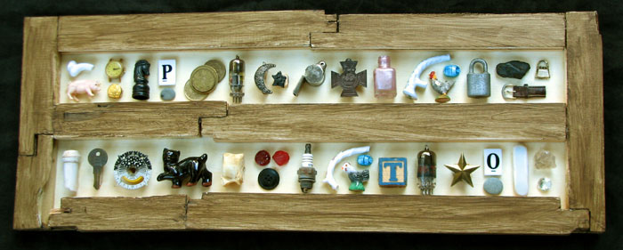 """Snooty's Hieroglyphics"" assemblage sculpture. found objects, wood, adhesive, acrylic paint. 24.25 in x 9.25 in x 2 in."